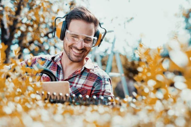 man trimming using face and ear protection and gas powered hedge trimmer
