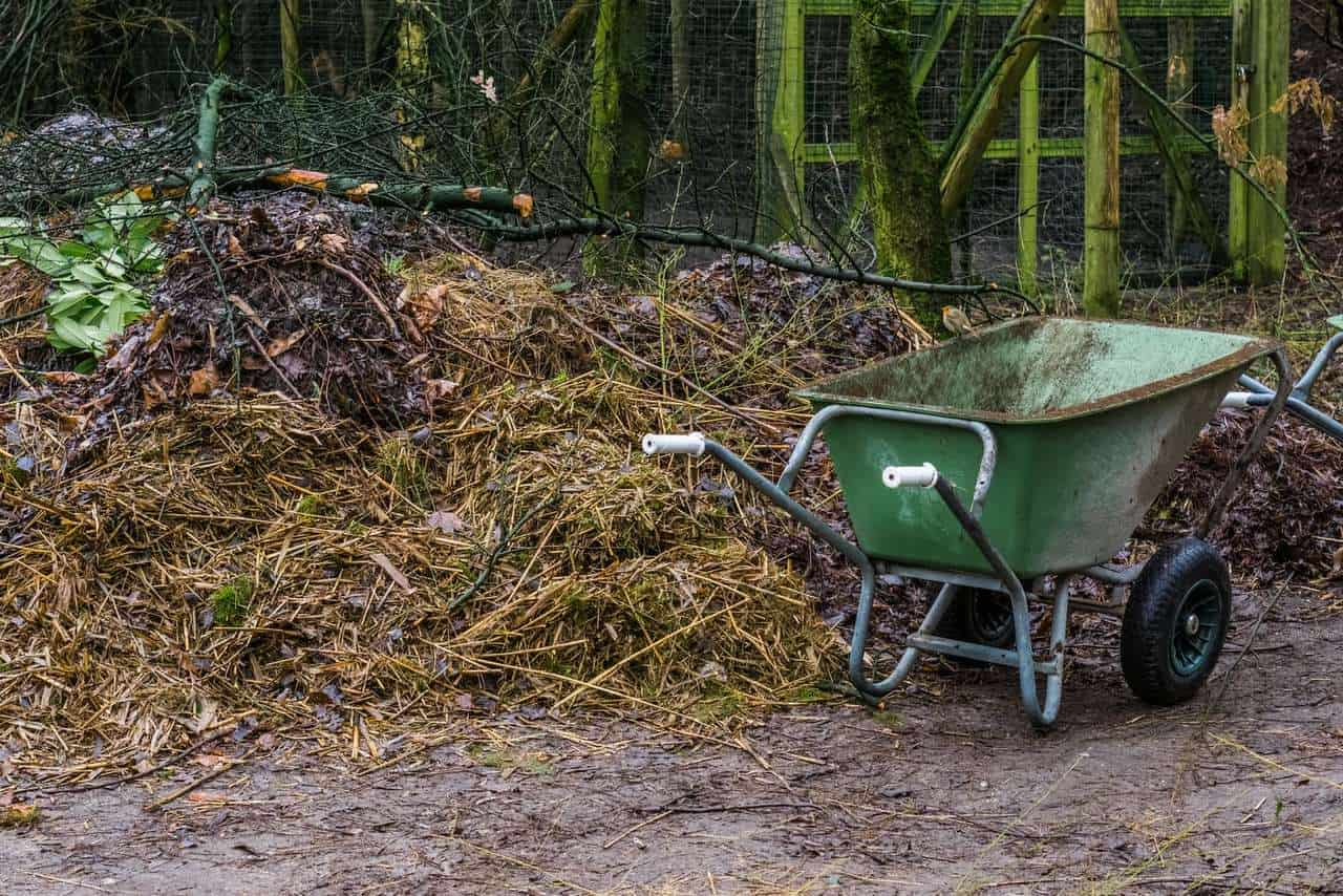 wheelbarrow next to a compost pile